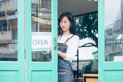 woman hanging open sign on door of business
